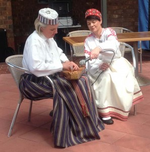 Two ladies in Latvian National costume playing the kokle, a Latvian musical instrument